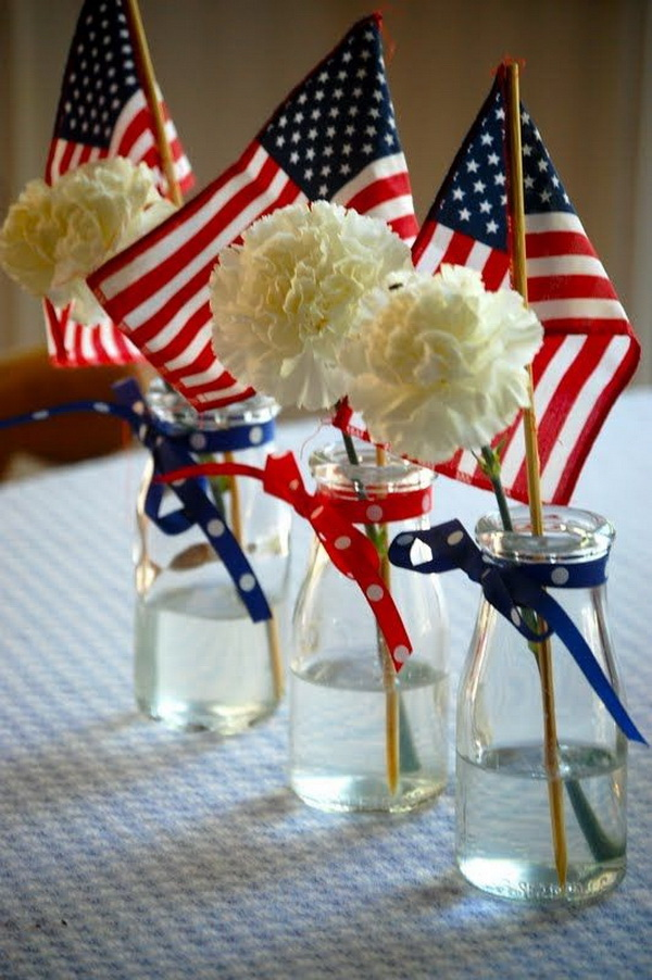 Fill the clear glass vase with a white carnation and an American flag and finished with ribbons. So easy and fun for a national table decoration!