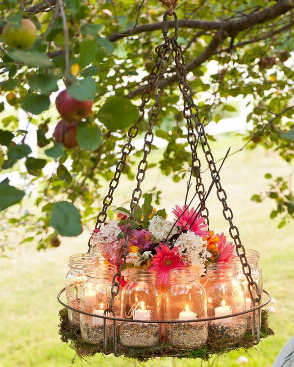 DIY Mason Jar Garden Chandelier. What a unique and awesome garden chandelier for your outdoor! All you need are a shallow tray, canning jars, votive candles, moss, a flowerpot, rope, chain, and birdseed to make your own one!