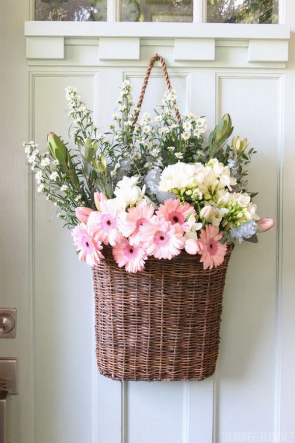 Basket Flower Arrangement. Rustic baskets are used as containers to hold the arrangements. This basket flower arrangement make a perfect front door hanger during the spring season and add a touch of shabby chic charm.