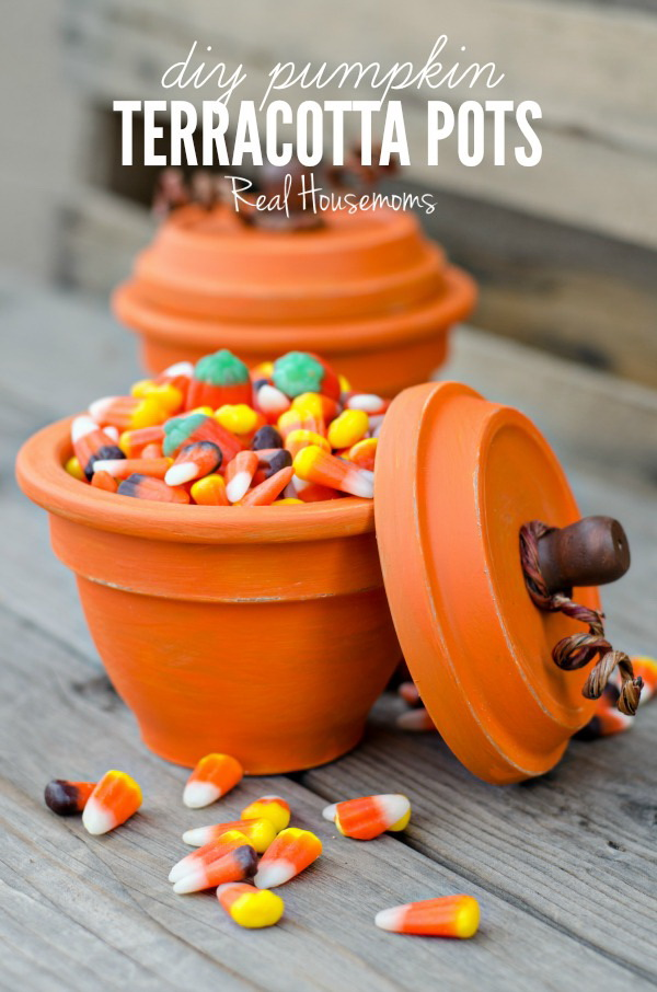 DIY Pumpkin Terracotta Pots. Turn an ordinary garden terracotta pot into an festive terra cotta pumpkin with candy corns inside! They surely brighten up your home for Fall and this Tahnksgiving Day.