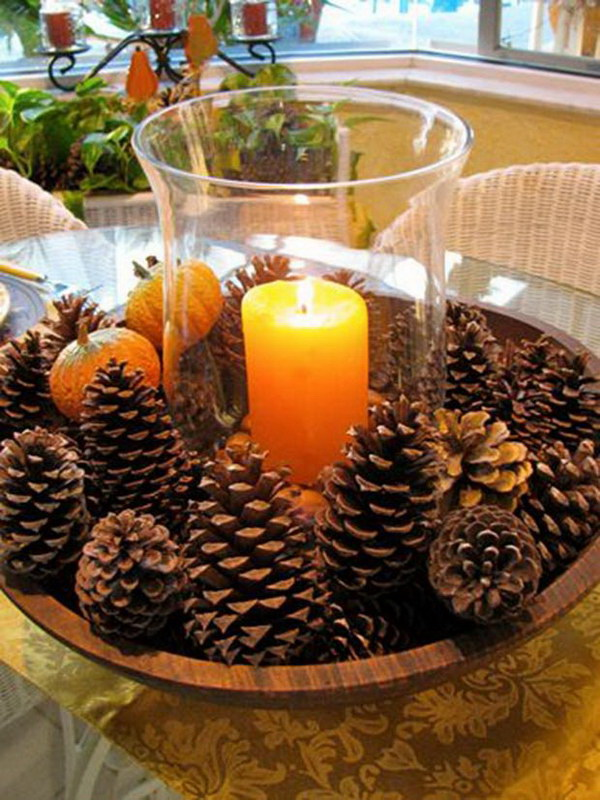 DIY Fall Centerpiece with Pine Cones. Simply arrange pine cones in natural colors around the big glass candle holder with a lighting candle inside. An elegant fall centerpiece to beautify your dinner table.