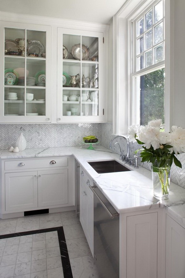The backsplash tile is a Carrara Bianco Herringbone. Elegant kitchen with glass-front cabinets, stainless steel appliances, marble countertops, a single-bowl sink, contemporary white cabinets, white marble backsplash.