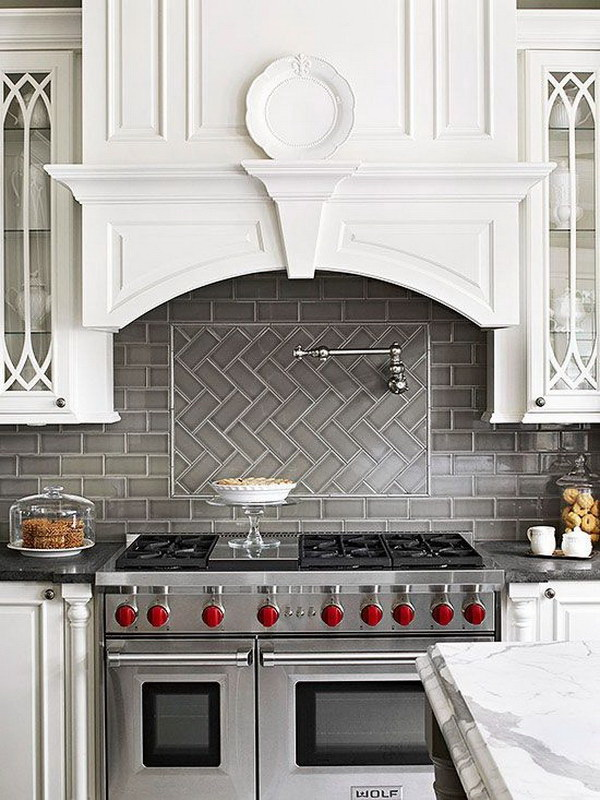 Grey herringbone subway tile backsplash works great with the stainless stove and the white cabinetry.