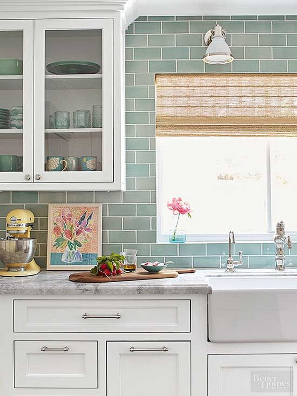 Subway tiles in seafoam green give the kitchen a color kick. Run to the ceiling, the smooth, glossy tiles also provide a textural changeup from all the wood. Bright white cabinetry with traditional recessed panels supplies plenty of neutral color to the fresh palette.