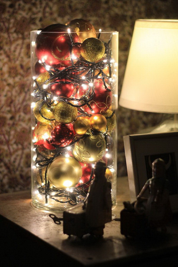 Christmas Ornaments and Lights in a Glass Vase. What an easy but stunning way to display your holiday ornaments and lights in a clear glass vase! Great for your living room or bedroom!