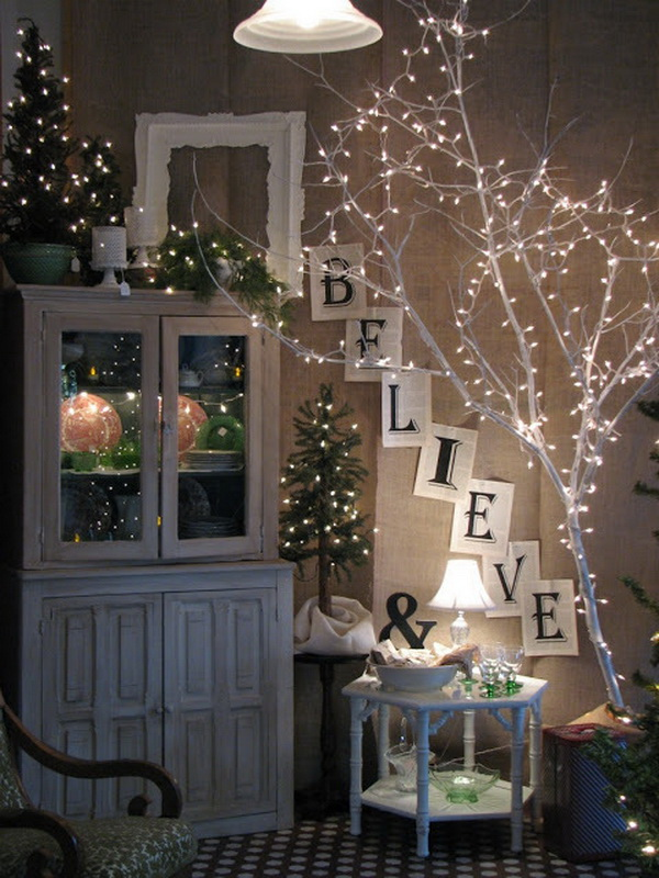 """DIY Lighted Branches. Bring a tree branch indoor, spray paint it and wrap it in lights! The lighted branches look so appealing paired with the white tree branch draped in lights and the slanted """"BELIEVE"""" sign leading up to the top of the cabinet and the tallest mini tree on the far left. It is also great for outdoors decoration for this Christmas and winter."""