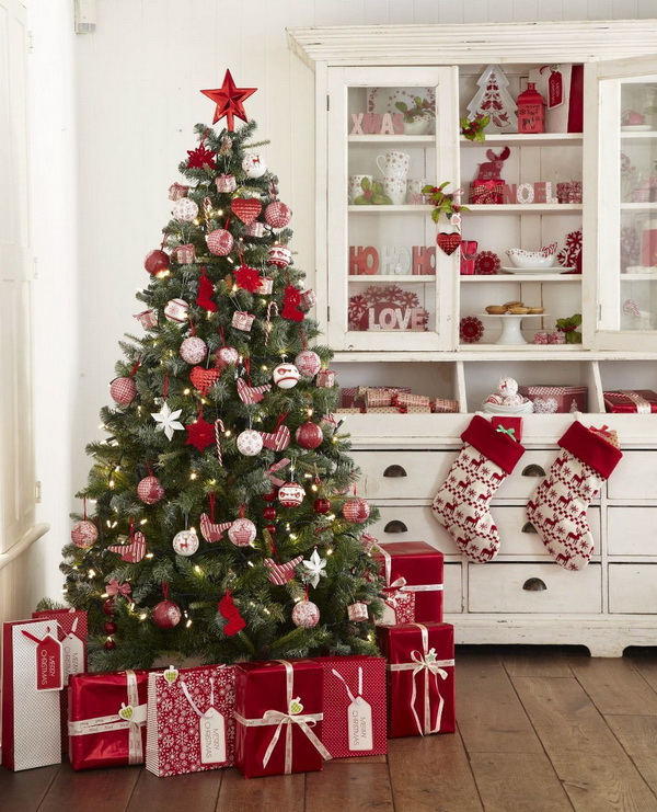 Green Christmas tree decorated with traditional red and white Christmas decorations and paired with red themed present boxes arround.