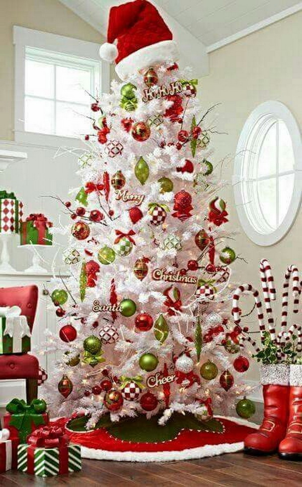 White Christmas tree with red and green decorations. A Santa hat as the topper looks so lovely and adorable!