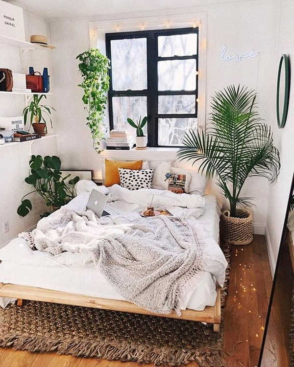 Bohemian style bedroom with fresh and natural green plants in the corner of the mattres.