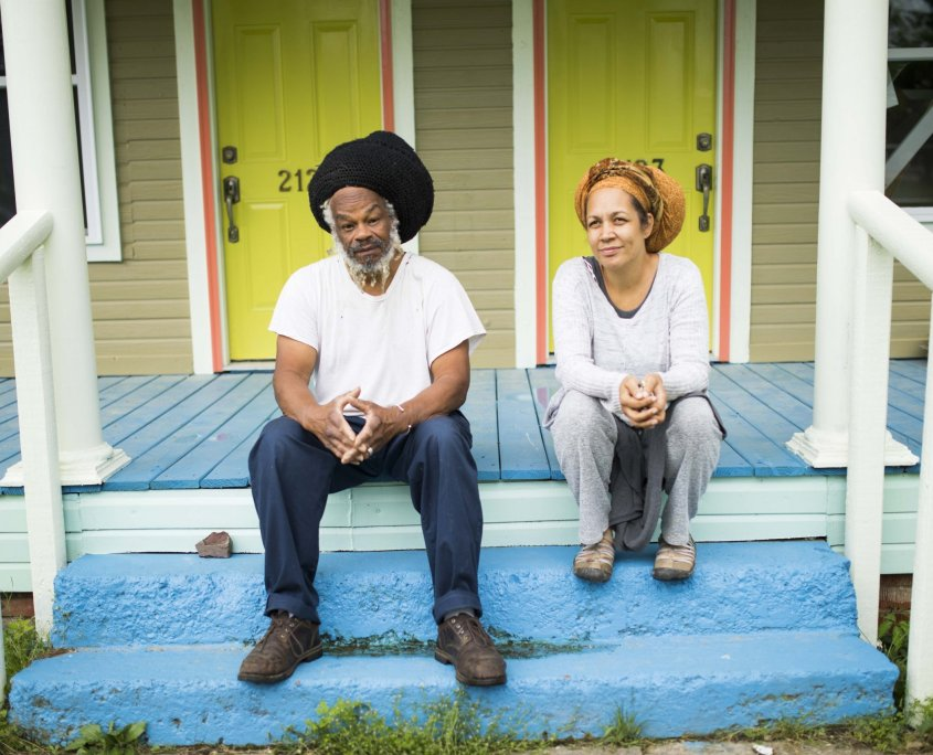 Two smiling people sit on a top porch step