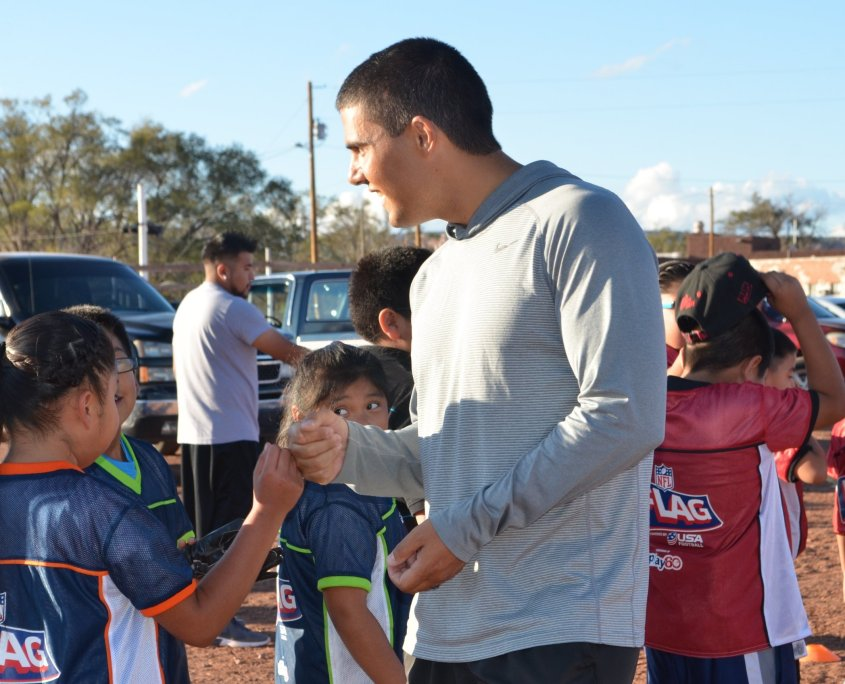 Joseph Claunch of the Zuni Youth Enrichment Project, stands, turned slightly away from camera, engaging with children.