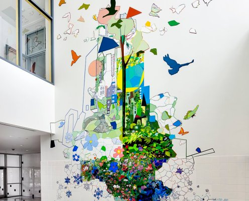 A colorful mosaic mural climbs up a white wall