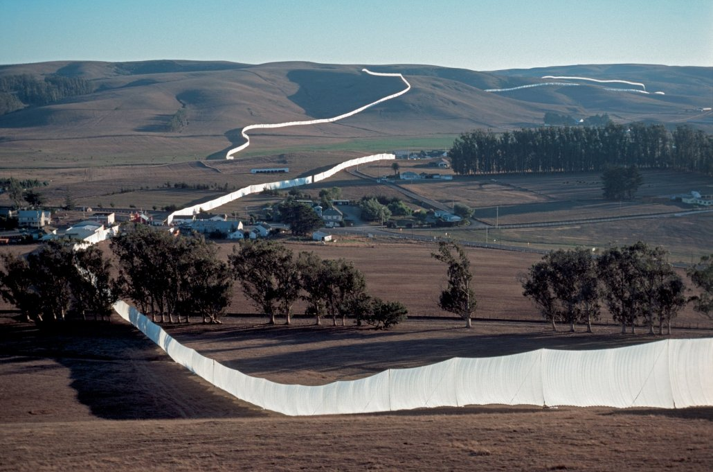 a tall white fabric fence stretches across the horizon over several hills