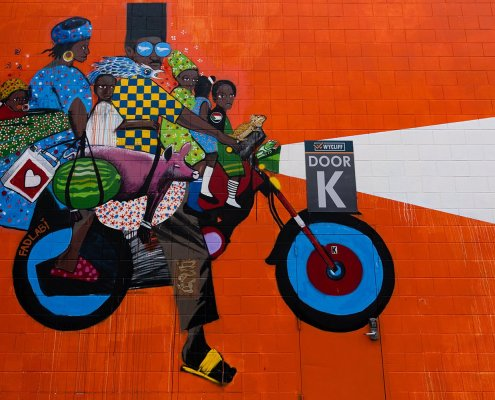 A colorful mural depicts a group of folks riding the bak of a motorcycle