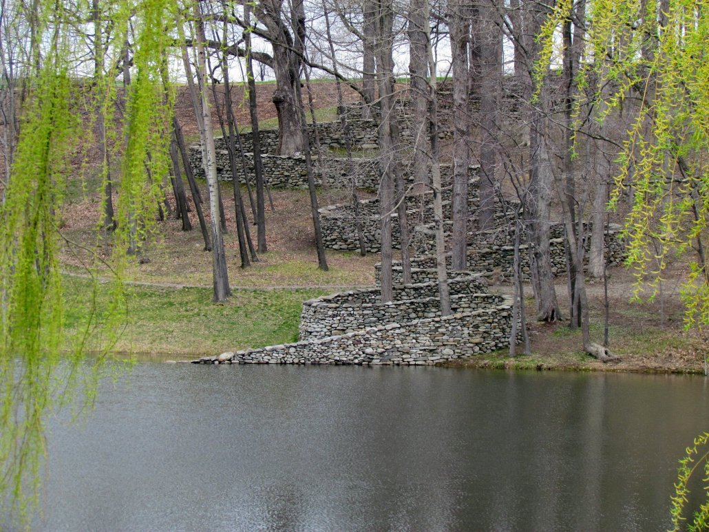 a stone wall handbuilt by stonemasons snakes through the trees down a hillside sweeping back and forth in the trees as it reaches the water and tapers down into the water