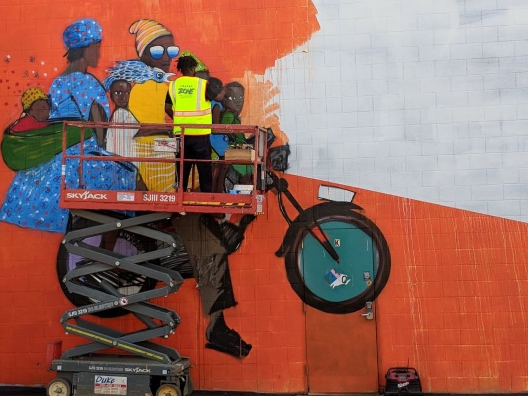 an artist stands on scaffolding as he paints a colorful mural of a family of Black figures riding a motorcycle together