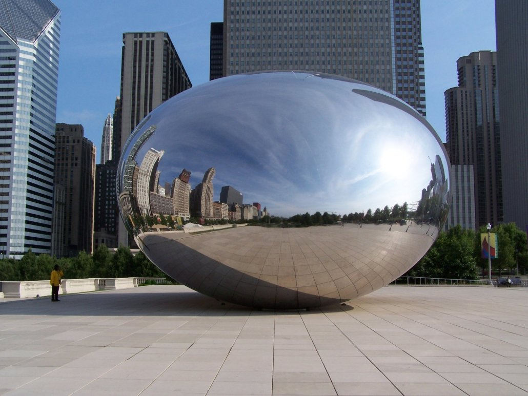 the smooth mirrored surface of the bean-like sculpture reflects the city of chicago