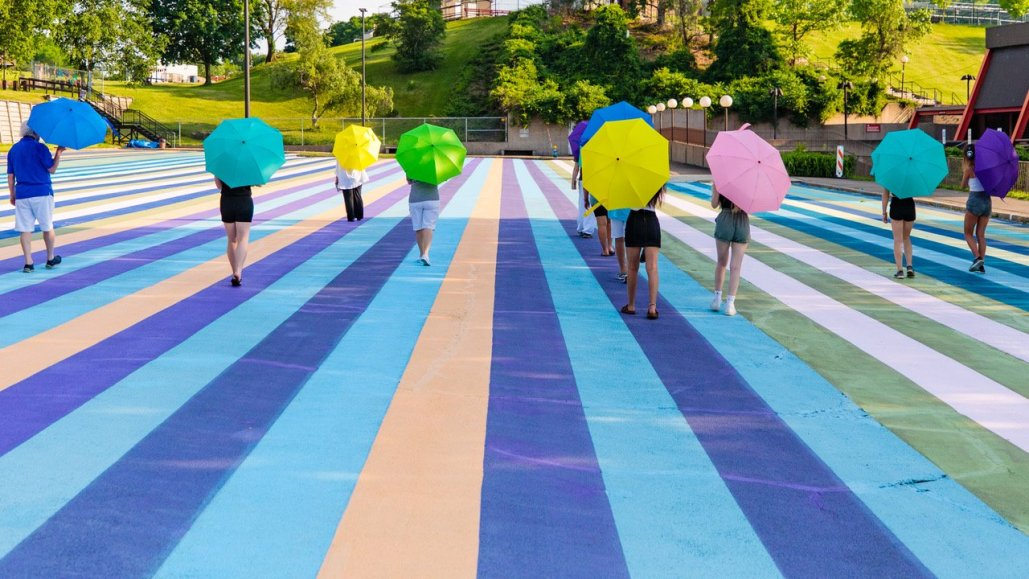 people walk away from the camera holding colorful umbrellas, below them is a ground painted with colorful stripes leading away from the camera
