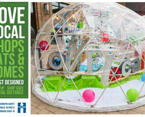 a clear plastic dome structure sited on a sidewalk is filled with creative paraphernilia