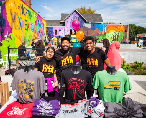 a group of young people stand outside together in an area covered with art