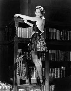 Portrait of a young woman standing on a chair and dusting a bookshelf in a sexy outfit