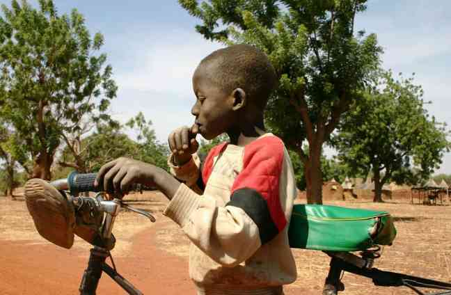 child with a bicycle in burkina faso