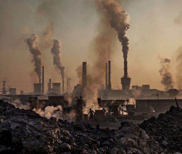 Smoke Billows From A Large Steel Plant As A Chinese Laborer Works At An Unauthorized Steel