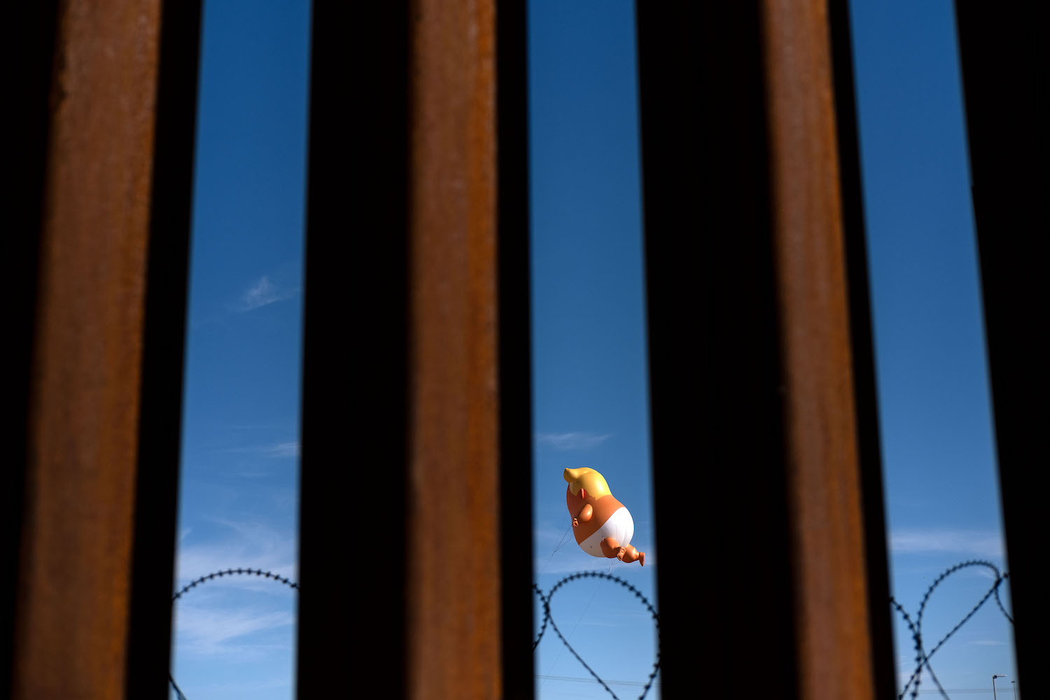 A satirical balloon of a baby U.S. President Donald Trump is seen through the U.S.-Mexico border fence during a demonstration prior to Trump's visit to Calexico, California on April 5.