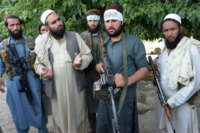 Taliban fighters and local residents celebrate the ceasefire on the second day of Eid in the outskirts of Jalalabad on June 16,2018.