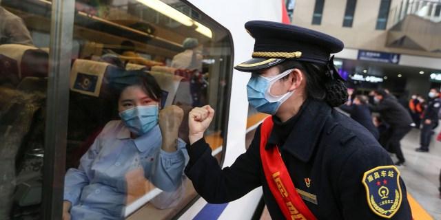 Obsługujący pociąg gestykuluje wsparcie personelowi medycznemu, gdy 13 lutego wyjeżdżają do Wuhan w Nanchang, w chińskiej prowincji Jiangxi.