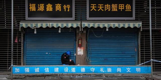 Strażnik siedzi przed zamkniętym hurtowym targiem owoców morza Huanan, który został powiązany z przypadkami koronawirusa w Wuhan w Chinach, 17 stycznia.