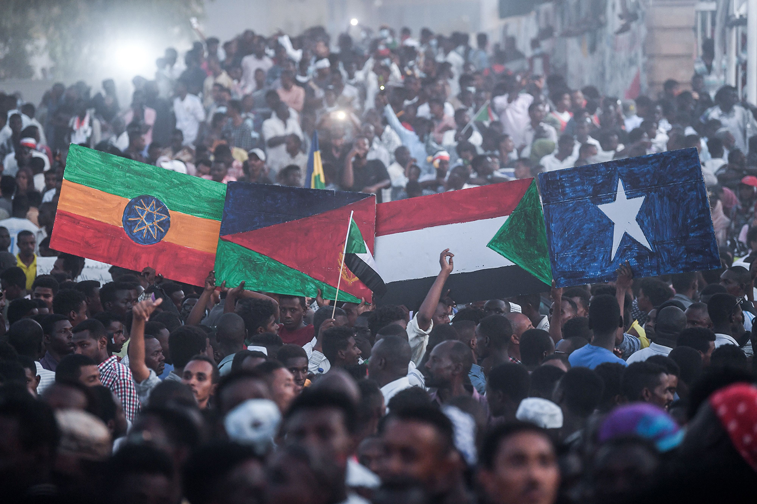 "Sudanese protesters hold national flags of Ethiopia, Eritrea, Sudan, and Somalia as they gather for a march outside the army headquarters in Khartoum on April 25, 2019. Tens of thousands of protesters converged from all directions on Sudan's army headquarters after calls for a ""million-strong"" demonstration to demand the ruling military council cede power."
