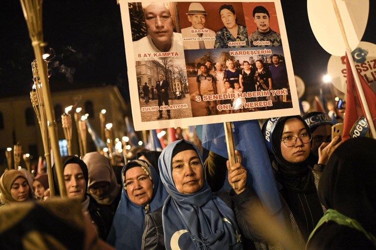 Supporters of China's Muslim Uighur minority hold torches and placards of people allegedly killed in the country's so-called reeducation camps during a demonstration in Istanbul on Dec. 20, 2019.