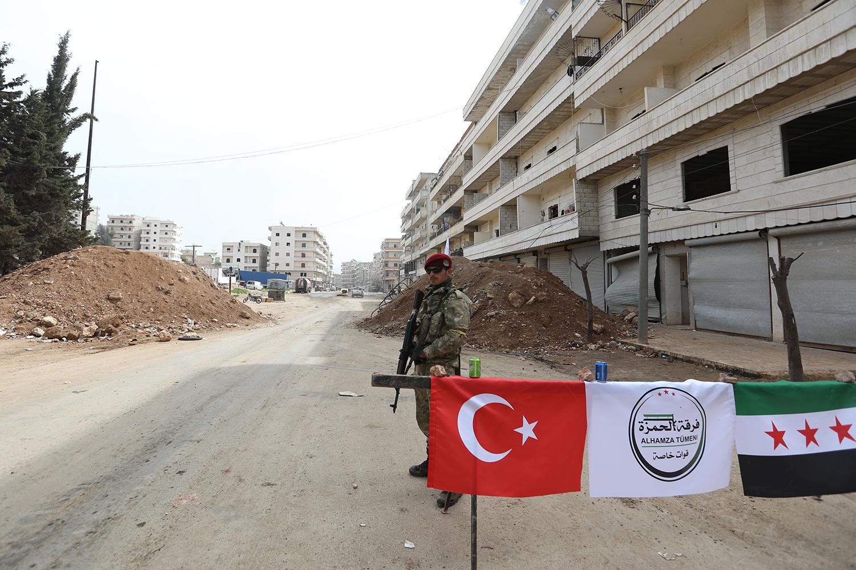 Rebel with gun at roadblock in Syria