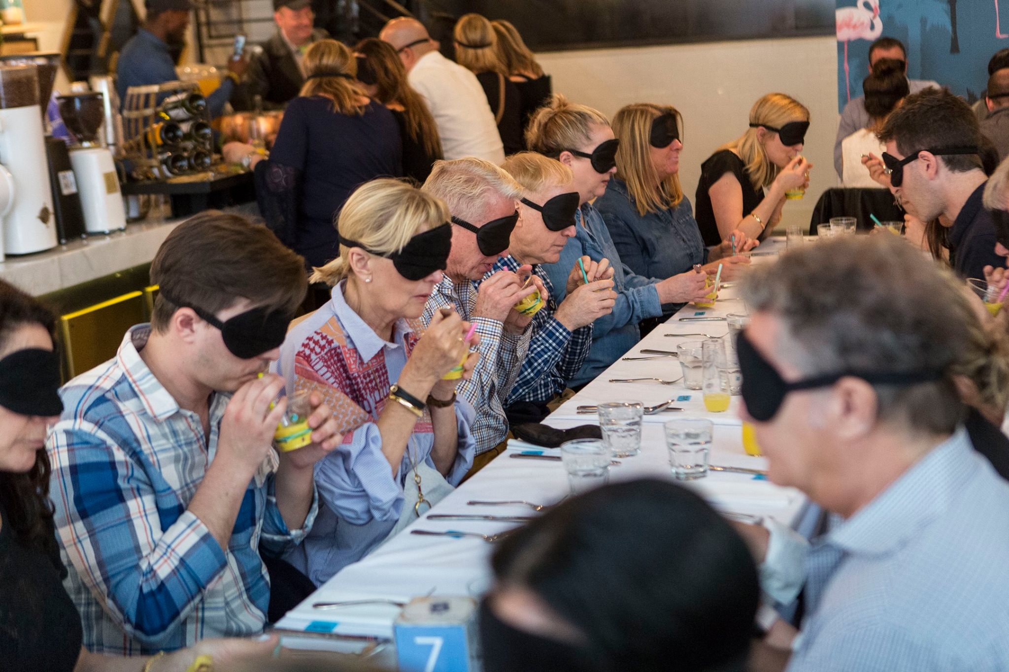 Brunch attendees blindfolded and drinking fruit drink