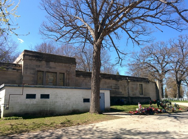 The white crematory building still stands behind the mausoleum. Decorations removed from the graves after the winter stand collected to one side. Photo by Kevin Walters.
