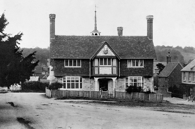 A historical photo of the Forest Row Village Hall from around 1904. Shows the hall with a small picket fence surrounding the main entrance, with dirt roads all around.