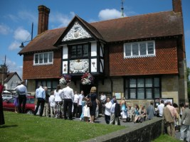 A photo of the Forest Row Village hall in 2008. The image is of a wedding reception party mingling on the front lawn near the war memorial.