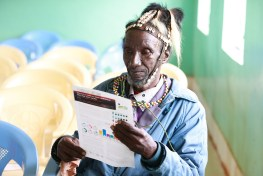 Village elder wearing a headdress reading the Itare-Chemosit Sub-Catchment Management Plan (SCMP) for forestry and water governance in Kenya Rau Valley