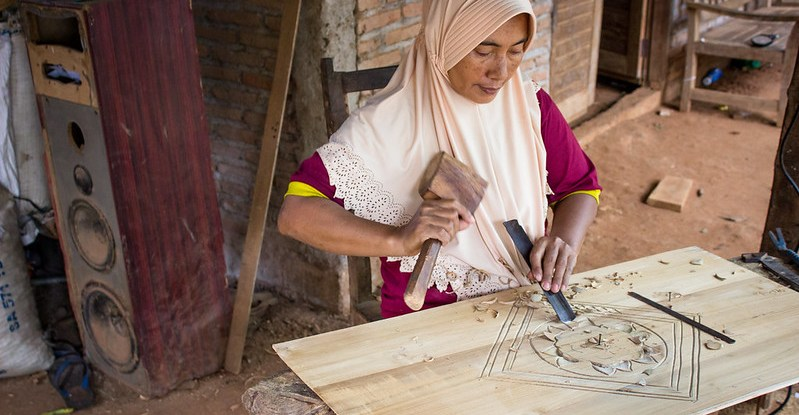 Woman chisels a design into wood
