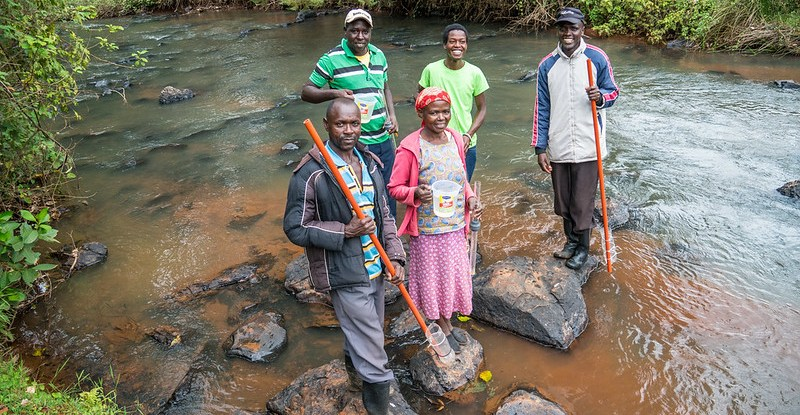 A group of five people stand on rocks in a river, some of them holding sticks with plastic water bottles attached to take samples