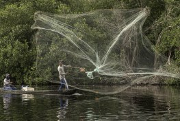 Men in boats cast fishing nets over the water