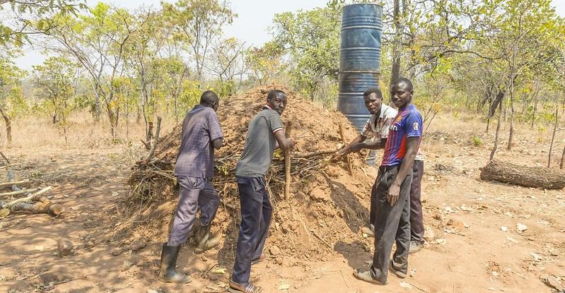 Men prepare a charcoal mound