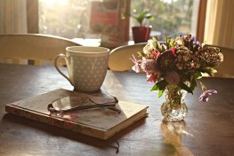 Tea cup, book, glasses and a small vase of flowers on a table