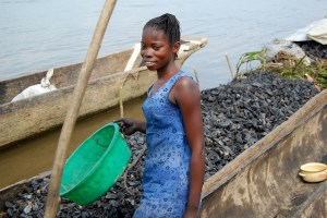A woman unloading charcoal from river boats in Africa. Photo by Jolien Schure for Center for International Forestry Research (CIFOR).
