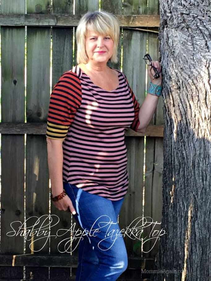 54 year old modeling Shabby Apple asymmetrical color top outside by tree