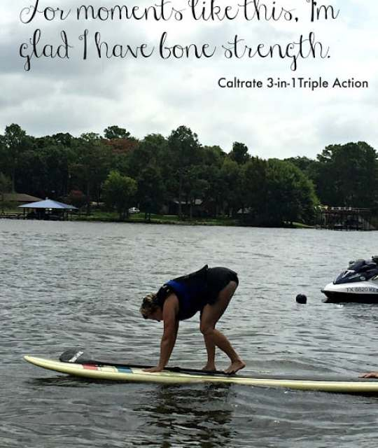 Midlife lady trying to stand up on paddle board in lake