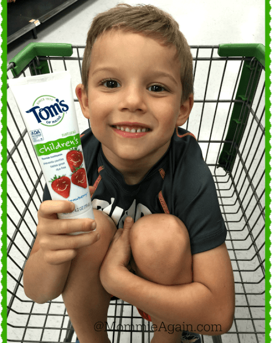 Young boy sitting in grocery cart at Walmart holding Tom's of Maine Children Silly Strawberry toothpaste