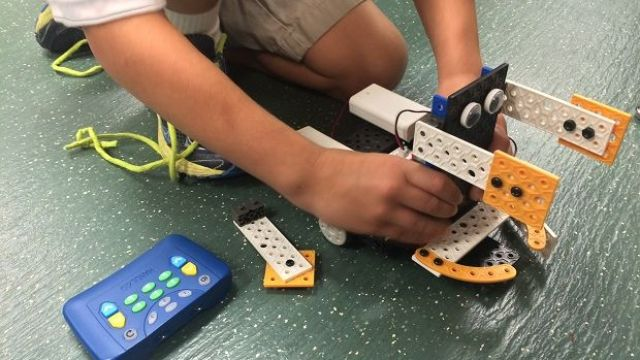 Boy playing with robot that he put together