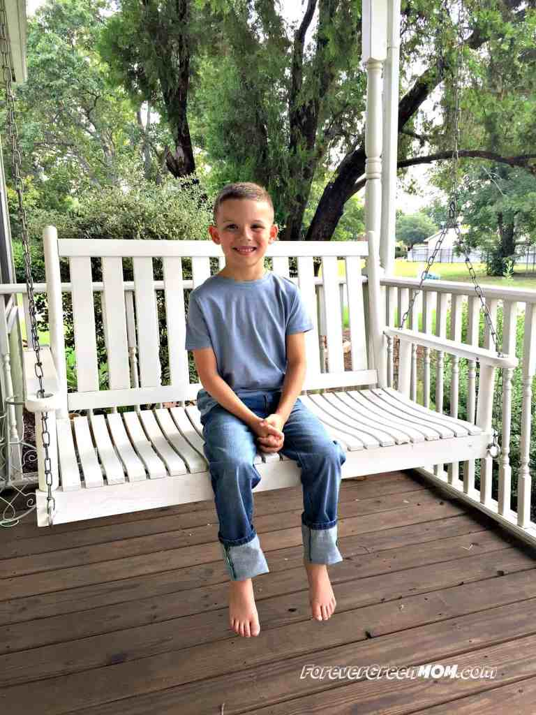 Mini_Boden_jeans_blue_tee_boy_sitting_on_swing